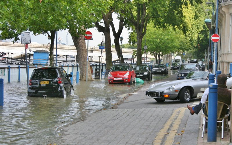 E Type Jag sees a flooded road and reverses away fast.