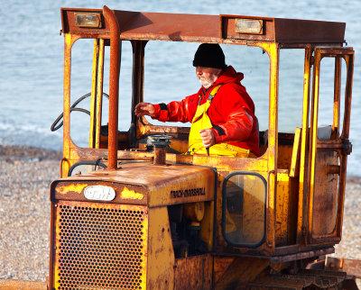 Fisherman driving bulldozer pulling crab boat up the beach.