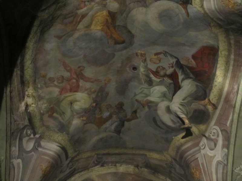 the ceiling includes a sculpted leg and foot projecting from the arched painting