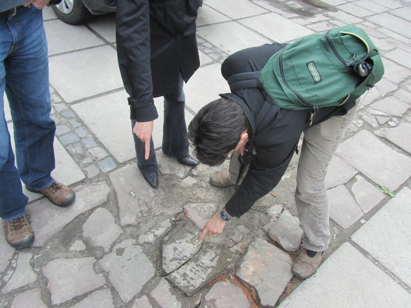 Alex F. with a headstone used as paving on the square where the central synagogue once stood