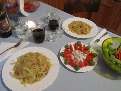 fried cabbage, herring with tomatoes and olives, and salad