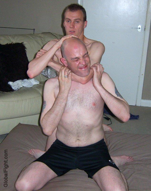 boy putting brother in necklock dads son fighting hard.jpg