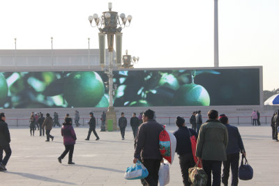The pedestrians in the square seem oblivious to the huge images on the screen