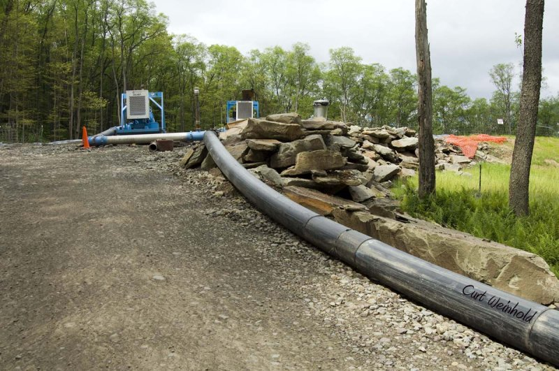 Pipe from drill rig leads to holding water pit