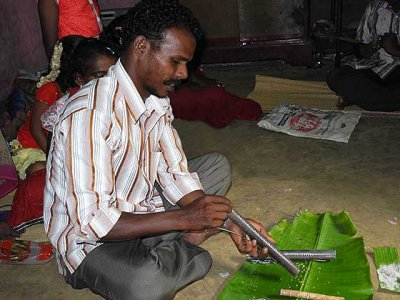 Kani shamanism. Before the ceremony grains of rice are poured down the kokkara. Tirunelveli District, Tamil Nadu.