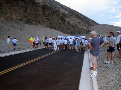 6 am runners gather at the start line banner. its 101F/38C with 21% humidity (twice the usual)