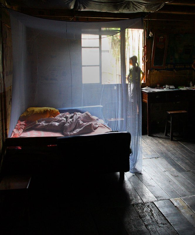 the netted bed. Remote village, China. 2006