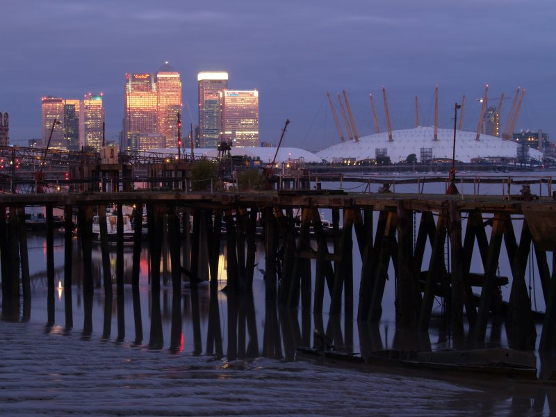 An old wooden pier,with the grandeur of Canary Wharf,behind
