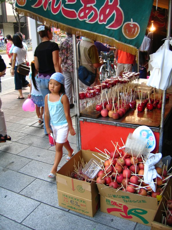 Pouting girl next to candied fruit stand