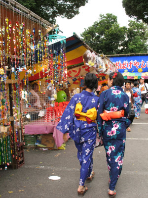 Yukata girls walking past a charm stall