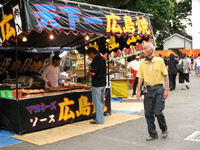 Hiroshima-yaki stand and passing local
