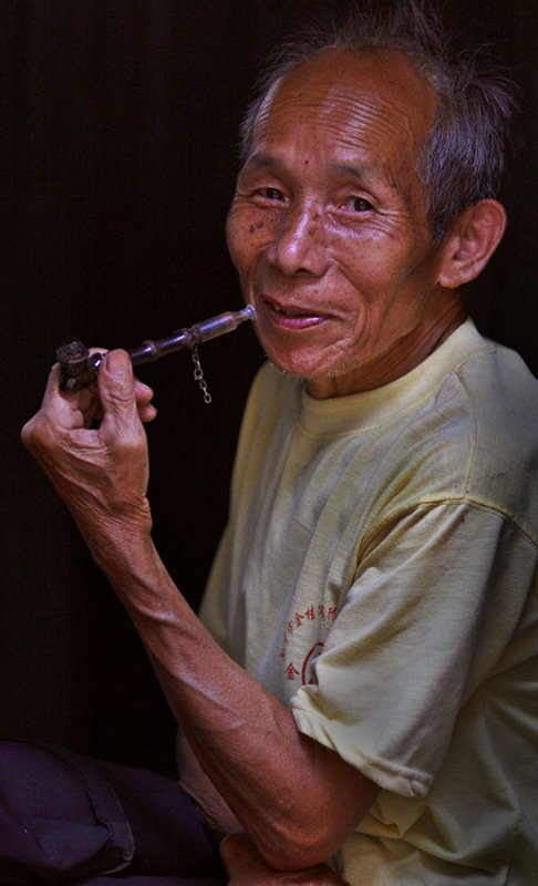 Kam elder with traditional bamboo and ceramic pipe.
