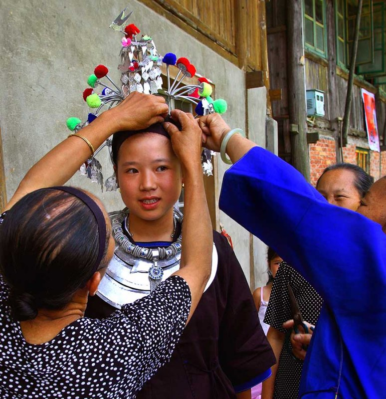 3182 Young Kam womans headdress being placed for drum tower dedication.