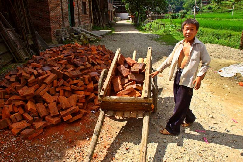0271 Young boy loading bricks that he will haul to a construction site.
