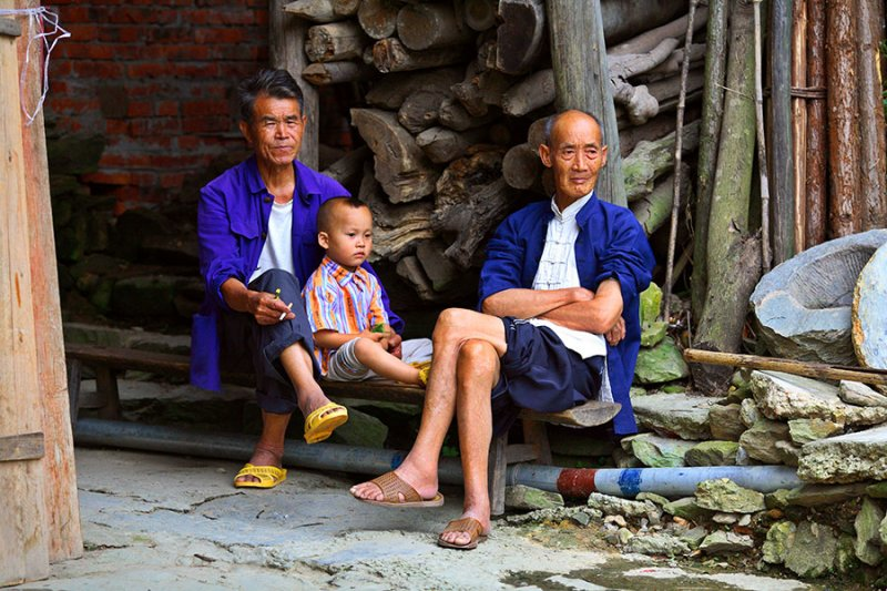 4429 Two Kam men and boy relaxing in central section of village.