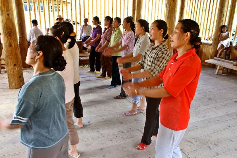 0576 Women practice singing and dancing.