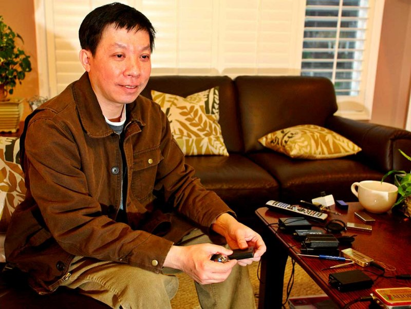 Dr. Xin Feng holding holding two of his creations the Micro IV and Mini IV headphone amplifiers.