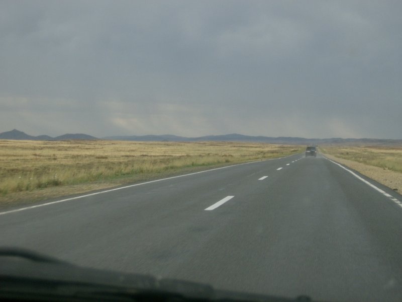 Rain in distance and recently here going by the car ahead
