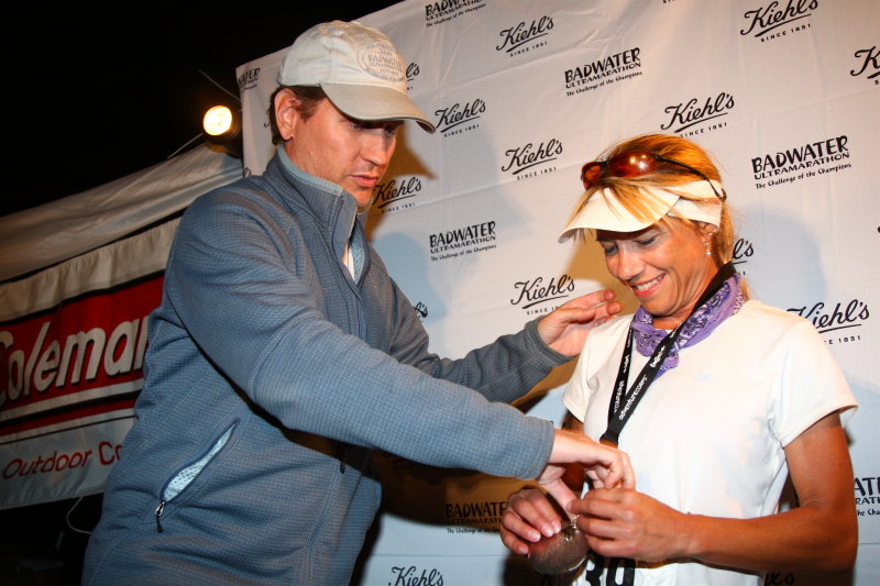 Chris Kostman, Race Director, presents the finishers medal
