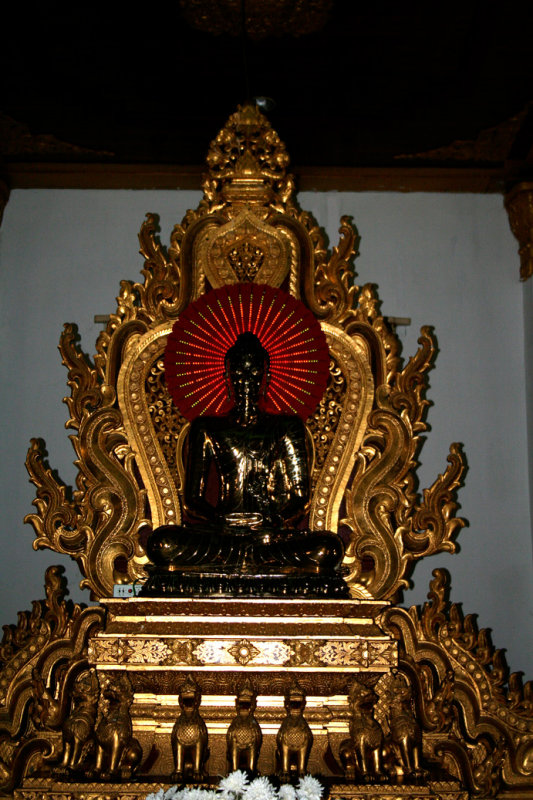 A Buddha in the prayer hall of Atumashi Monastery.  Note changing electric lights of the halo.