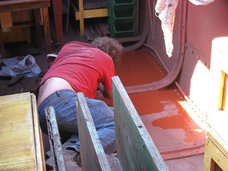 Martin paints one of the floor panels after having removed the old paint and de-rusted it using an angle grinder