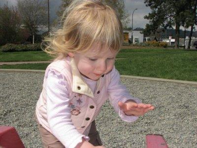 Dad sprinkles pebbles down the slide.