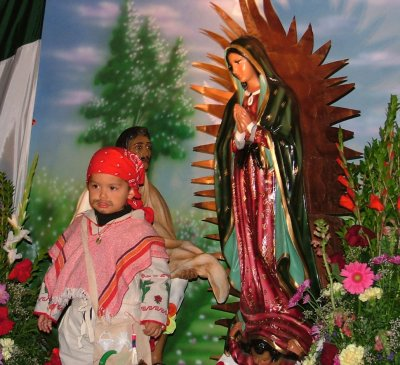 A little boy dress asJuan Diego poses for a photo with the Virgen de Guadalupe
