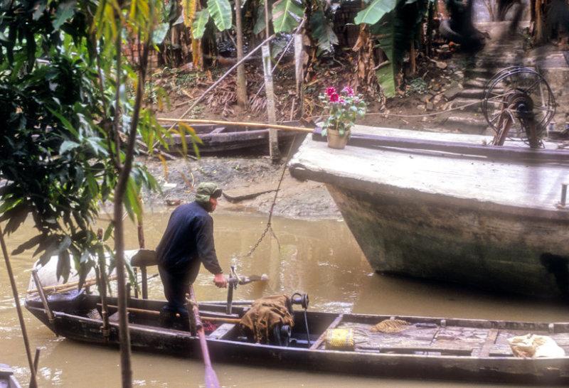 Boatman On A Cannal Outside A Big City