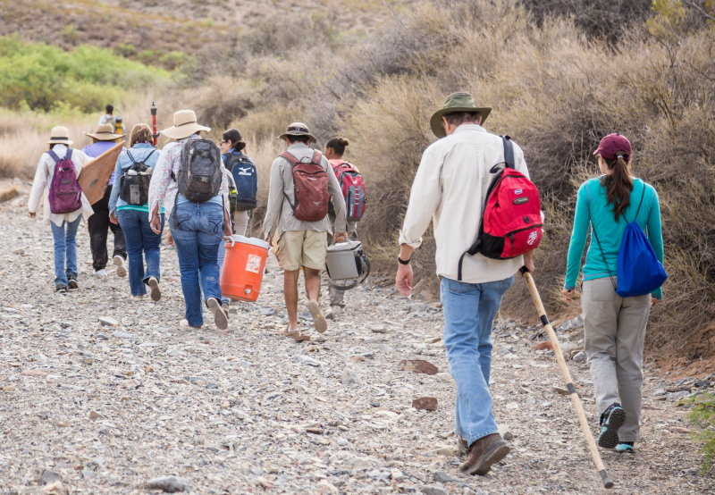 Crew carrying gear from vehicles to the site followed by visitors Dr. Warren DeBoer and Dr. Mary Alice Scott
