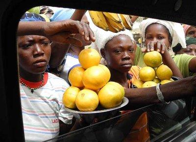 Women try to sell their fruit through car windows, Burkina Faso