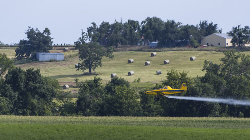Crop Duster with Hay Bales in Background