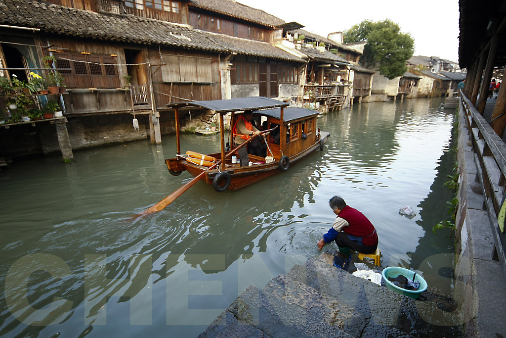A woman washes her clothes in the water of the canal.