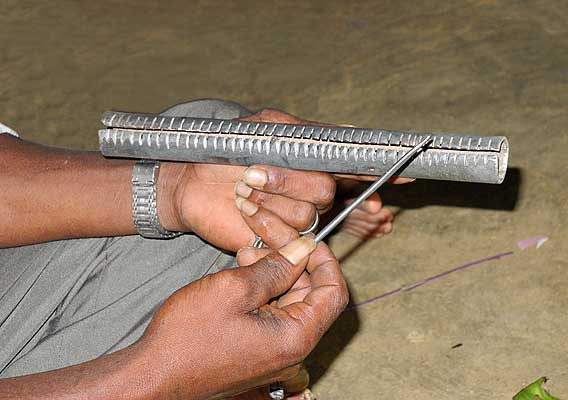 During the ceremony the shaman uses an iron nail to make music on the kokkara. Tirunelveli District, Tamil Nadu.