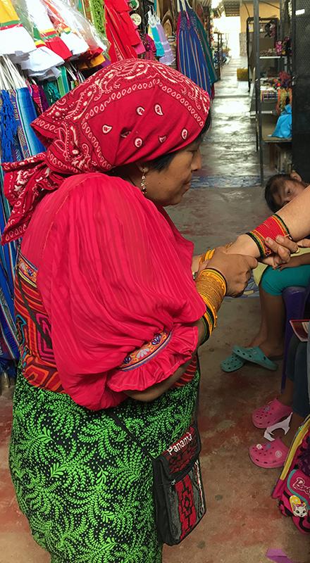 Kuna woman winding the beaded bracelet on my arm