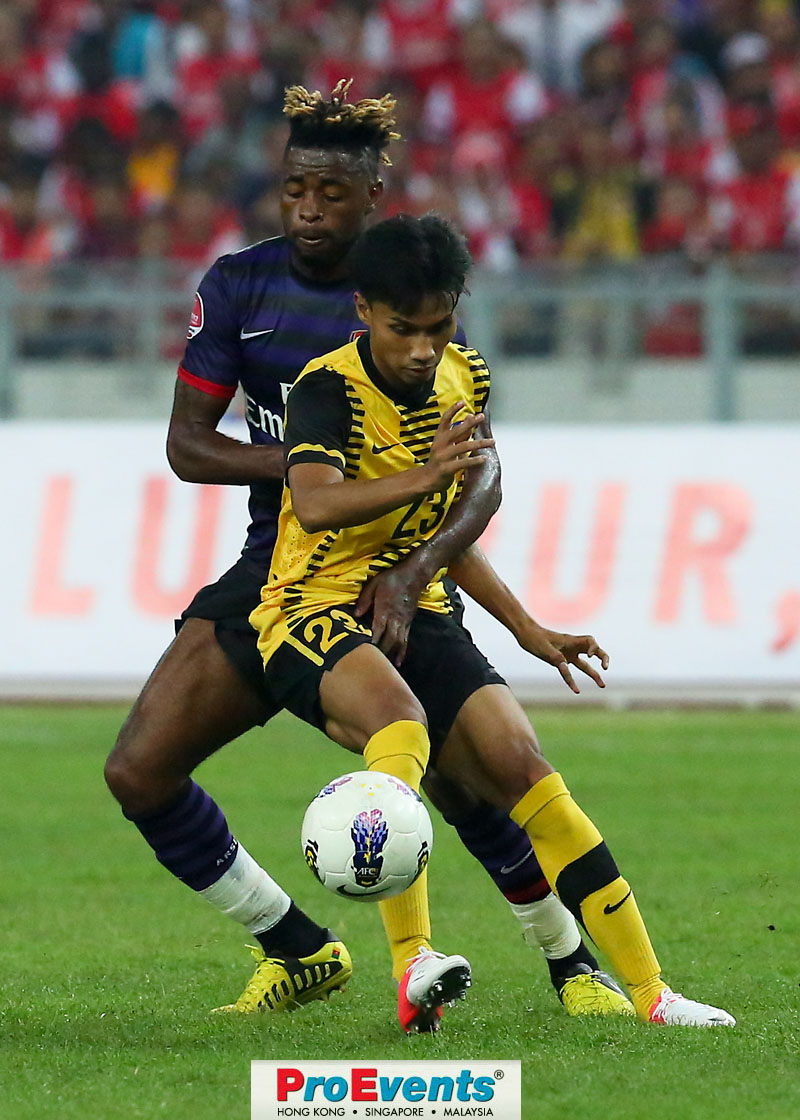 Alex Song shielded by a Malaysian player