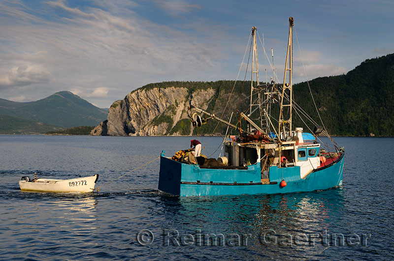 Fishermen leaving East Arm Bonne Bay at Norris Point at the end of the day with Shag Cliff