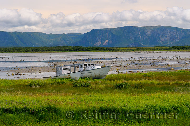 Abandoned boats at Parsons Pond Newfoundland with Gros Morne Long Range Mountains