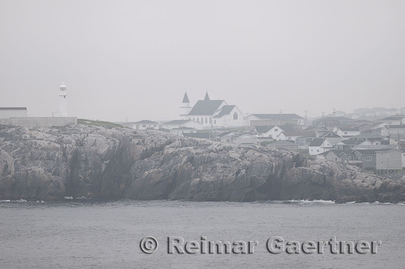 Channel Port aux Basques Newfoundland lighthouse and Anglican church from the coast in fog