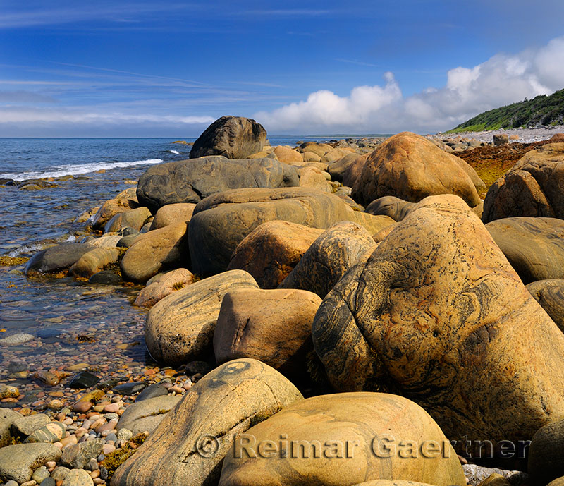Smoothed rust colored boulders on the shore of Martins Point where SS Ethie sank in 1919