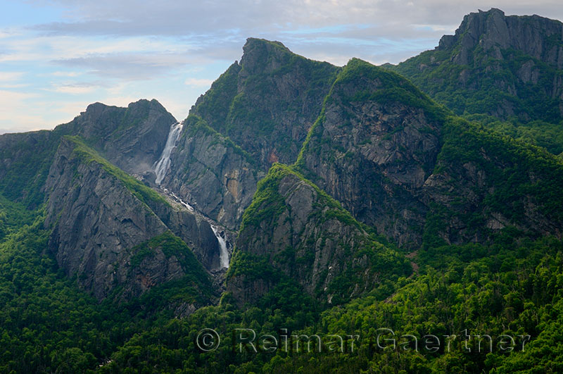 Waterfalls plunging into Western Brook Pond with steep rock cliff at Gros Morne National Park Newfoundland