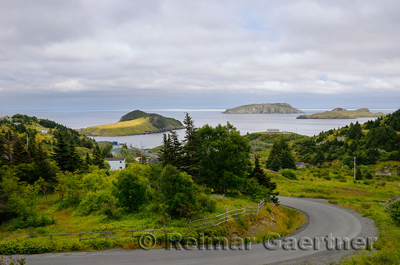 Road winding down to Tors Cove harbour with Fox Island and Great and Ship Island bird sanctuaries Newfoundland