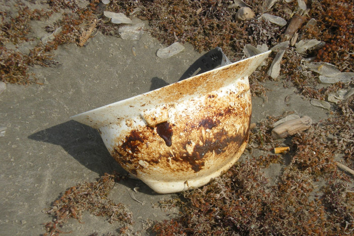 Oiled Hard hat washed up on beach.