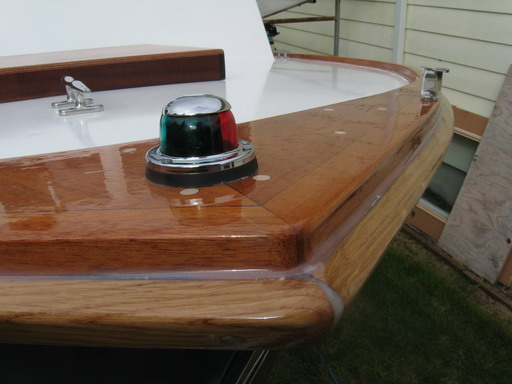 Closeup of bow light and bow chock.  Sheer guard will get white paint; toe rail, bright.