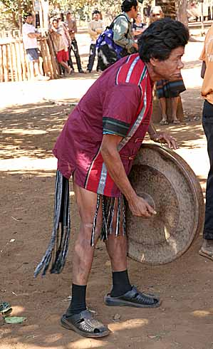 Man playing the biggest gong in Kameng, Cambodi.a.