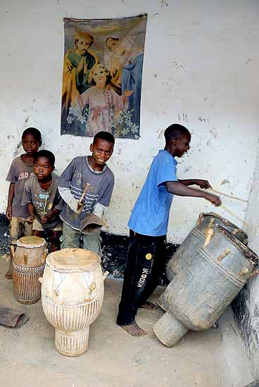 Priest Kwabena Adade´s children play the drums under a poster of the Holy Family.