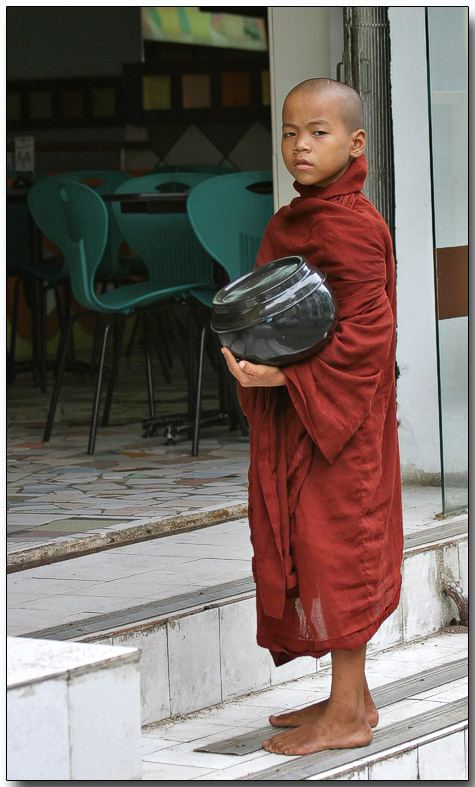 Novice monk with alms bowl waiting for breakfast