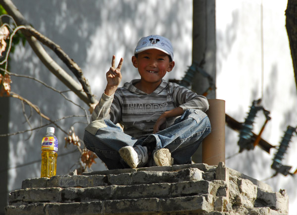 Friendly boy posing up on a perch, old town Tsetang