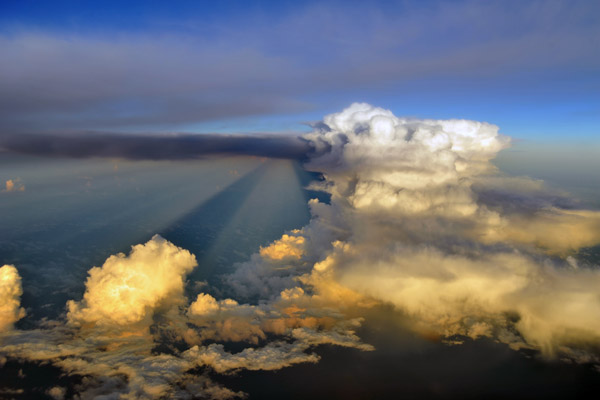 Thunderstorm and CB casting long shadow early in the morning off Borneo, Indonesia