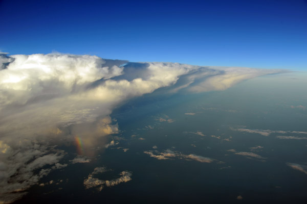 Thunderstorm with a huge anvil and small rainbow off southern Borneo