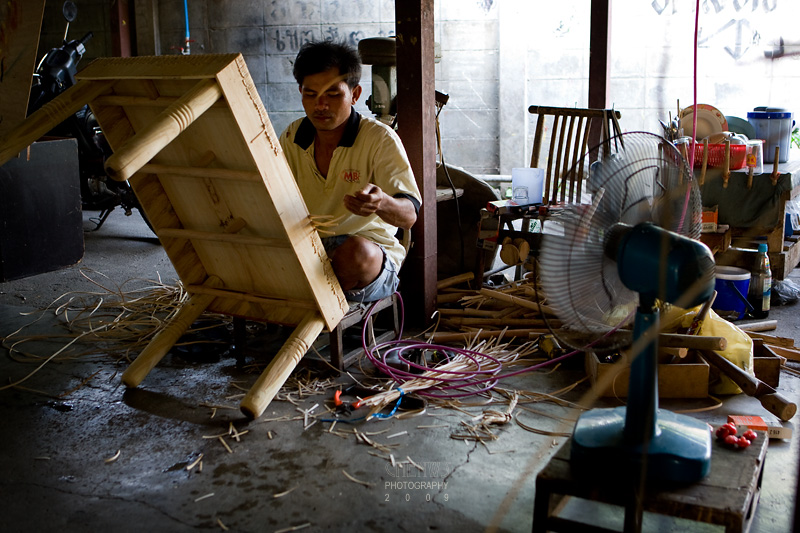 A craftsman making a rattan table.